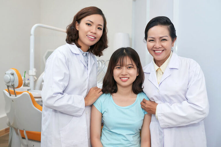 smiling-doctors-with-girl-in-dental-office-LHWA2P6-768x513